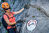 A woman at the via ferrata indicates icon key place, Absamer via ferrata, bettelwurf, Karwendel, Tyrol, Austria