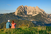 A man and a woman sitting on meadow and views of the Wilder Kaiser mountain, in the dawn, from behind Wilder Kaiser, Kaiser mountains, Tyrol, Austria