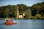 group of people in swimsuits relax at motorized float, view from Glienicke Bridge at royal garden of Babelsberg, Potsdam, Brandenburg, Germany