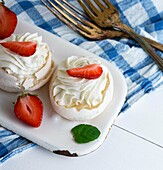 Meringue cakes with cream and fresh strawberries, close up.