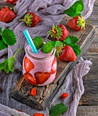 Yoghurt with fresh strawberries, milk smoothies in a glass jar with a straw on a gray wooden table, top view.