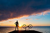 Seaton Carew, County Durham, north east England. United Kingdom. A mountain biker looks out over the North sea at sunrise.