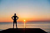 Seaton Carew, County Durham, north east England. United Kingdom. A jogger looks out over the North sea at sunrise.