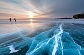 Two persons walking over a flat ice with cracks on the lake Baikal at sunrise, Irkutsk region, Siberia, Russia.