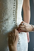 The mother of the bride helps her daughter button the wedding dress, Valencia, Spain