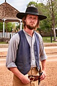 Adult young man dressed in vintage cowboy clothes at the annual Doc Holiday event in Tombstone, Arizona.