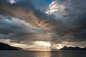 Sun breaks through cloud-cover off the Chilean coast, Beagle Canal, Alberto de Agostini National Park, Magallanes y de la Antartica Chilena, Patagonia, Chile, South America