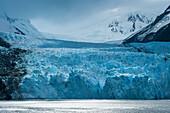 Sunlight backlights the craggy glacier and surrounding mountains, Garibaldi Glacier, near Beagle Canal, Alberto de Agostini National Park, Magallanes y de la Antartica Chilena, Patagonia, Chile, South America
