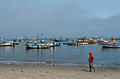 A man walks along the beach in front of a backdrop of fishing boats, Paracas, Ica, Peru, South America