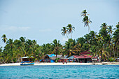Huts and a volleyball net are clustered among palm trees on one of the tiny islands, San Blas Islands, Panama, Caribbean