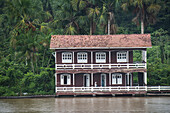 A noble looking two-storey house with a two-tiered wrap-around porch on two sides stands on the shore of the Amazon river, Breves Channels, near Belem, Para, Brazil, South America