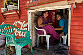 A woman and her son take a break from selling snacks and drinks in a small wooden structure next to one of the main streets of the town, Leticia, Amazonas, Colombia, South America
