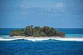 Waves break on the shore of a tiny island covered with palm trees, Bock Island, Ujae Atoll, Marshall Islands, South Pacific