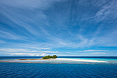 View of a tiny island covered with trees and surrounded by coral reefs and a long stretch of white sand beach, and dominated by a blue sky with airy, thin clouds, Likiep Atoll, Ratak Chain, Marshall Islands, South Pacific