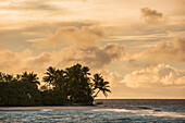 Late afternoon sun, light clouds and a low-lying, palm-covered island create a dreamy atmosphere, Likiep Atoll, Ratak Chain, Marshall Islands, South Pacific