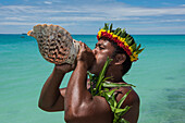 A man with flower-and-leaf crown blows into a large seashell to announce the arrival of visitors from an expedition cruise ship, Butaritari Atoll, Gilbert Islands, Kiribati, South Pacific
