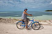 Eine Frau mit blauem Hut und langem Rock fährt ein blaues Fahrrad entlang des Wassers, Butaritari Atoll, Gilbert-Inseln, Kiribati, Südpazifik