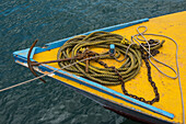 A yellow and blue bow of a small ship is strewn with yellow rope attached to a rusty chain and anchor, Lautoka, Viti Levu, Fiji, South Pacific
