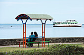 A young couple sits on a colorful resting place overlooking the shore, which features a boat leaning to port in shallow, low-tidal waters, Lautoka, Viti Levu, Fiji, South Pacific