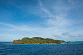 Small, tree-covered islands stand in turquoise water under a lightly clouded blue sky, Mata Utu, Uvea Island, Wallis and Futuna, South Pacific