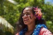 Eine schöne lächelnde Frau mit schwarzen Streifen auf den Wangen, einer bunten Blume im Haar und einer blauen Lei um den Hals bereitet sich darauf vor, Besucher von einem Expeditions-Kreuzfahrtschiff zu begrüßen, Fagamalo, Savai'i, Samoa, Südpazifik