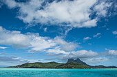 View of cloud-dotted skies over the verdant island, Bora Bora, Society Islands, French Polynesia, South Pacific