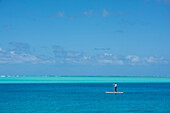 A lone standup paddle surfer wearing a long-sleeved shirt, a swimsuit, and a hat, paddles through dark-blue waters with shallower, lighter-colored water in the background, Huahine, Society Islands, French Polynesia, South Pacific