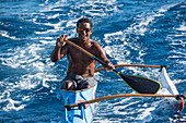 A young man wearing reflector sunglasses and paddling a single-rigger kayak smiles at the camera, Bora Bora, Society Islands, French Polynesia, South Pacific