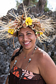 A local woman wearing a headdress of flowers and other plant material smiles at the viewer, Rimatara, Austral Islands, French Polynesia, South Pacific