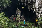 Zwei Männer und eine Frau, die bunte Kleidung tragen, stehen am Eingang einer riesigen Höhle, um Touristen als Besucher zu begrüßen, Rurutu, Austral-Inseln, Französisch-Polynesien, Südpazifik