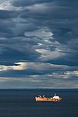 The ship Brecknock makes way under a dominating sky of dark, unusual clouds, Punta Arenas, Magallanes y de la Antartica Chilena, Patagonia, Chile, South America