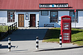 A typical red telephone booth stands in front of the Globe Tavern, one of the capital city's tourist attractions, Stanley, East Falkland, Falkland Islands, British Overseas Territory, South America