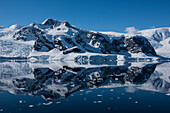 A rare, windstill moment allows the formation of an almost perfect mirror image of a wide mountain, Wilhelmina Bay, Antarctic Peninsula, Antarctica