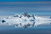 In a rare moment virtually devoid of wind, a mirror-image of snow-covered mountains with a central, high peak enchants the eye, Wilhelmina Bay, Antarctic Peninsula, Antarctica