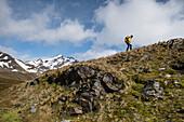 Ein Lektor von einem Expeditions-Kreuzfahrtschiff erklimmt einen steilen, grasbewachsenen Hügel, der mit aufragenden Felsen übersät ist, um einen Umkreis zu bilden, hinter dem die Passagiere angewiesen werden, sich nicht zu bewegen, Stromness, Südgeorgien