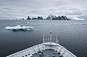 The bow of expedition cruise ship MS Bremen (Hapag-Lloyd Cruises) is visible as the vessel approaches a craggy, mountainous island surrounded by several ice-floes, Laurie Island, South Orkney Islands, Antarctica