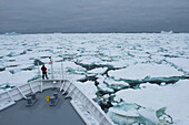A lone person stands on the so-called 'monkey bridge' of the expedition cruise ship MS Bremen (Hapag-Lloyd Cruises) amidst a mass of sea ice, near Laurie Island, South Orkney Islands, Antarctica