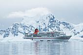 Das Expeditions Kreuzfahrtschiff MS Bremen (Hapag-Lloyd Kreuzfahrten), gesehen unter einem großen schneebedeckten Berg, schickt Zodiac Schlauchboote mit Passagieren zu einer malerischen Kreuzfahrt um die Bucht, Paradise Bay (Paradise Harbour), Danco Coast