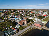 Aerial (drone) view of Stanley and the Christ Church Cathedral (1892), the world's southernmost Anglican cathedral, with its iconic Whalebone Arch at the corner, Stanley, Falkland Islands, British Overseas Territory