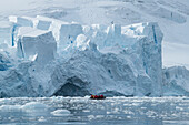 A Zodiac dinghy raft with passengers cruises through floating ice in front of a massive glacier front, Paradise Bay (Paradise Harbor), Danco Coast, Graham Land, Antarctica