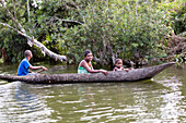 malagasy family paddling in dugout canoe on the Canal de Pangalanes, East Madagascar, Africa