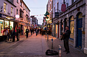 A street musician plays the guitar and sings, while Quay Street fills with pedestrians passing by on their way to their night out, Galway, County Galway, Ireland, Europe