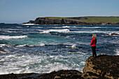 Bei einem Spaziergang an den Klippen von Kilkee betrachtet eine Frau in einer roten Jacke das aufgewühlte Meer während der Wind ihre Haare zerzaust, Kilkee, County Clare, Irland, Europa