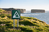 Danger! The edge of the cliff is not secured by fences or walls , and this sign warns walkers to watch their step, Kilkee, County Clare, Ireland, Europe