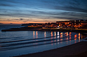City lights reflect in the water of the Atlantic Ocean at Kilkee Bay under a pink sky during sunset, Kilkee, County Clare, Ireland, Europe