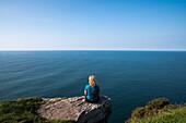 Eine blonde Frau sitz auf einem Felsvorsprung und blickt zum Meer, gesehen von einer Wanderung entlang dem Weitwanderweg Dingle Way, Ballydavid North, Brandon, Dingle Halbinsel, County Kerry, Irland, Europa