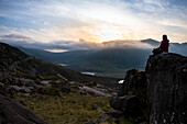 A woman sits relaxed on a rock and admires the sunset over the mountain pass with a vast panoramic landscape, seen from while walking the Dingle Way, Dingle Peninsula, County Kerry, Ireland, Europe