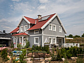 Gray two-story single family house with one dormer and a red roof in Nordic style with wooden facade, Korbach, Hesse, Germany, Europe