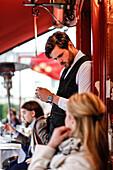 Kellner redet mit einer Touristin im La Mère Catherine Restaurant, Place du Tertre, Montmartre, Paris, Frankreich, Europa