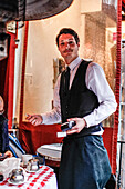 Waiter with the bill in one  hand at the La Mère Catherine restaurant, Place du Tertre, Montmartre, Paris, France, Europe